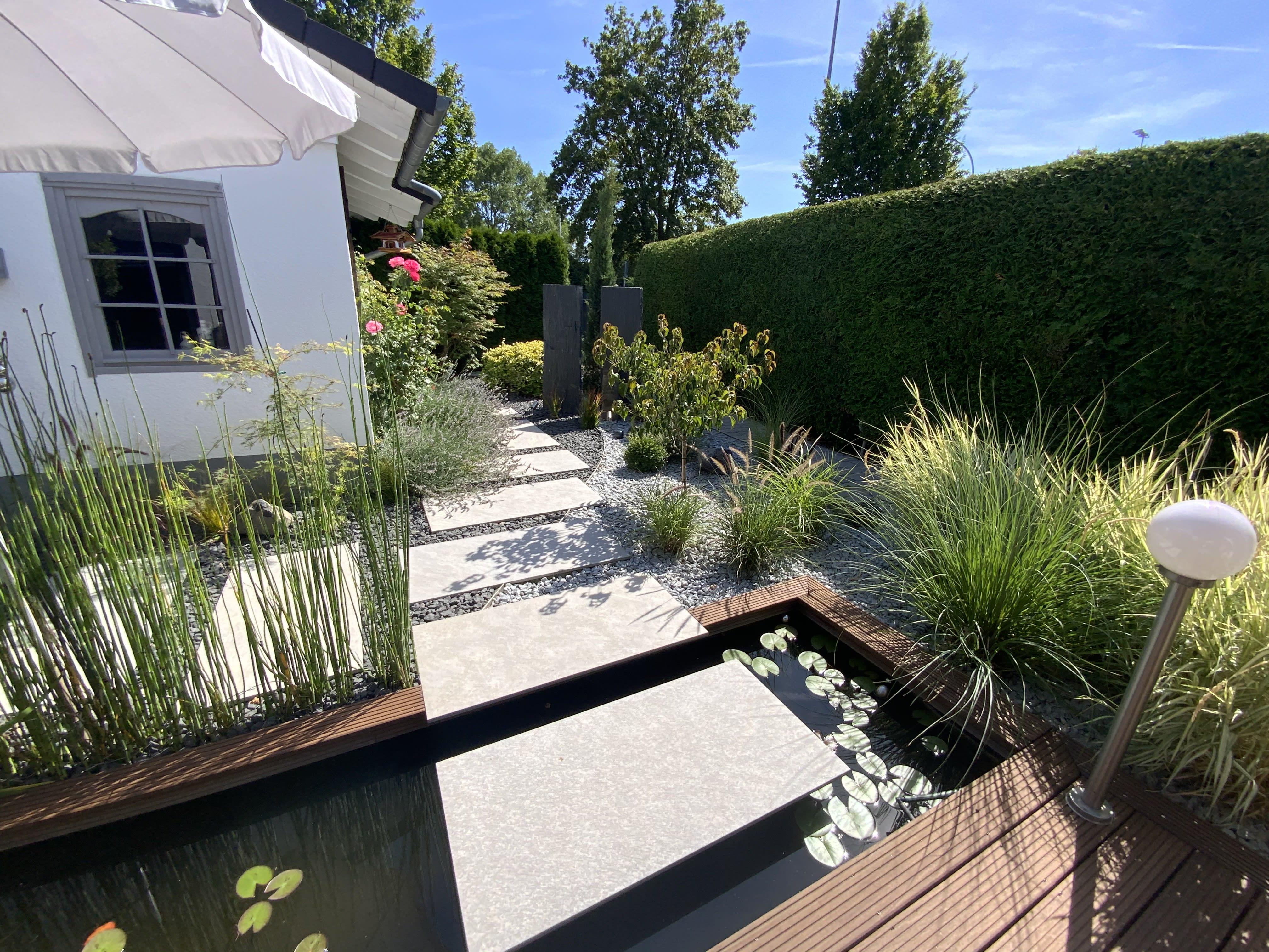 Garten mit Teich und Holzterrasse und Steinplatten von oben