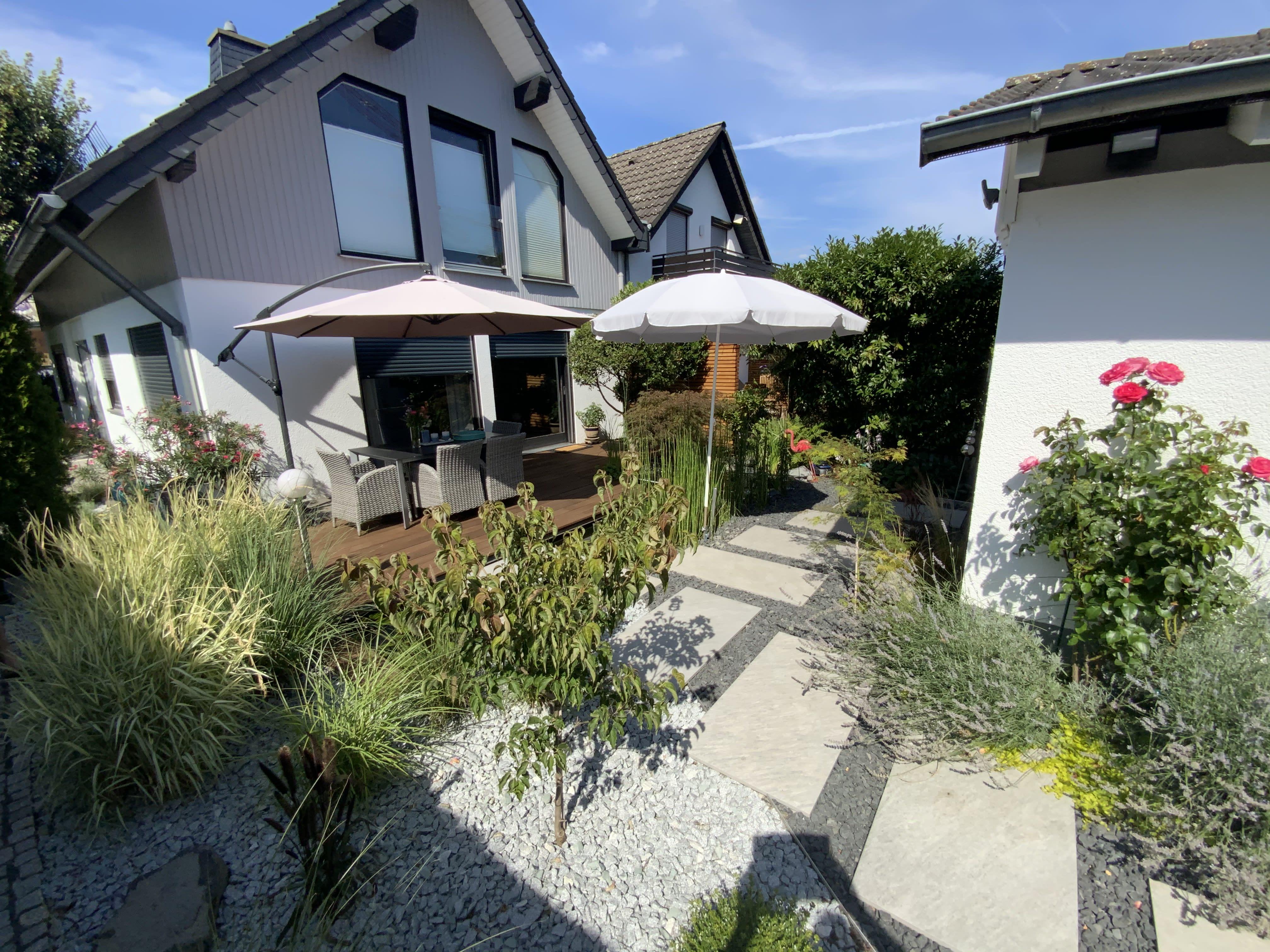 Garten mit Teich und Holzterrasse und Steinplatten Sicht auf Haus