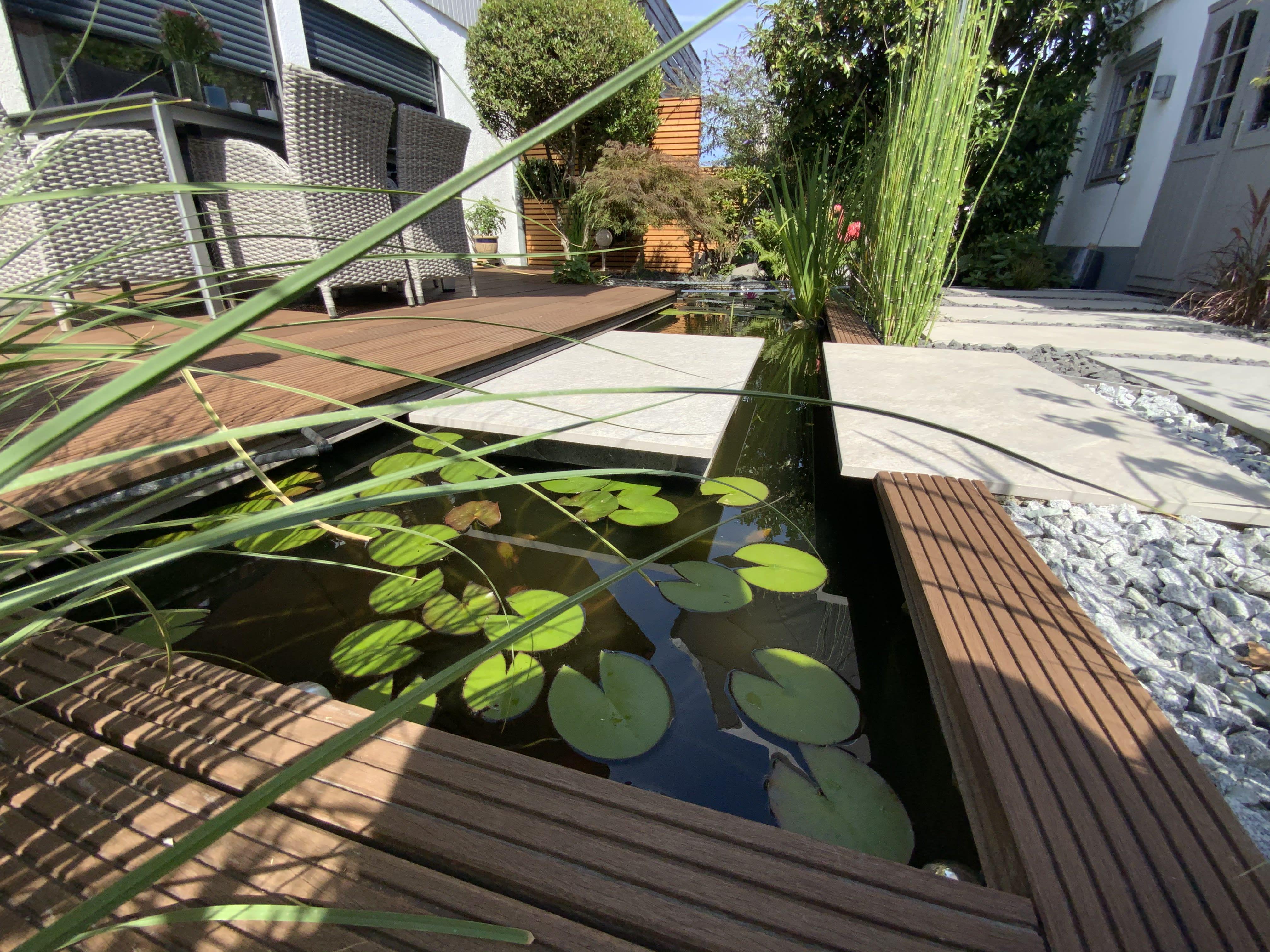Garten mit Teich und Holzterrasse und Steinplatten