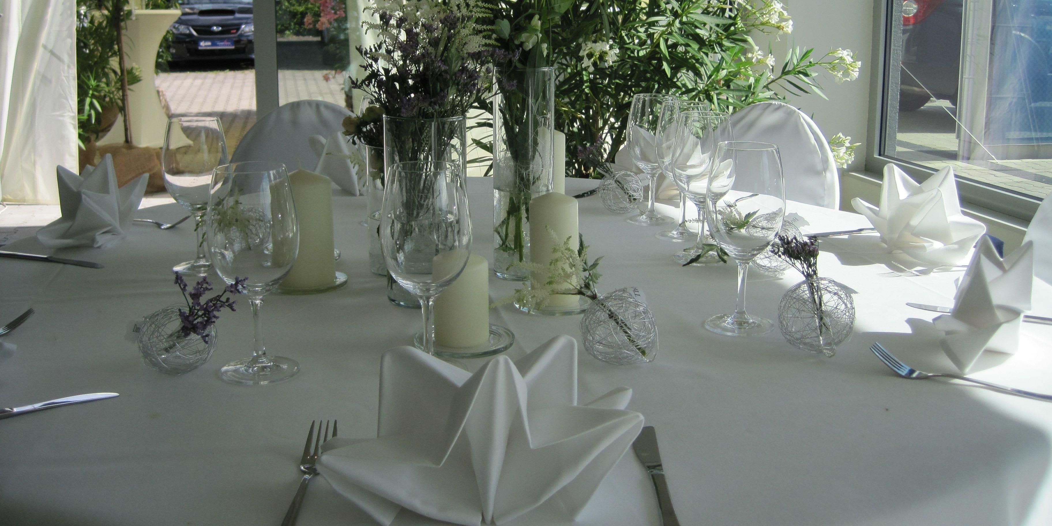Dekorierter Tisch weiß mit Blumenschmuck und Gläsern