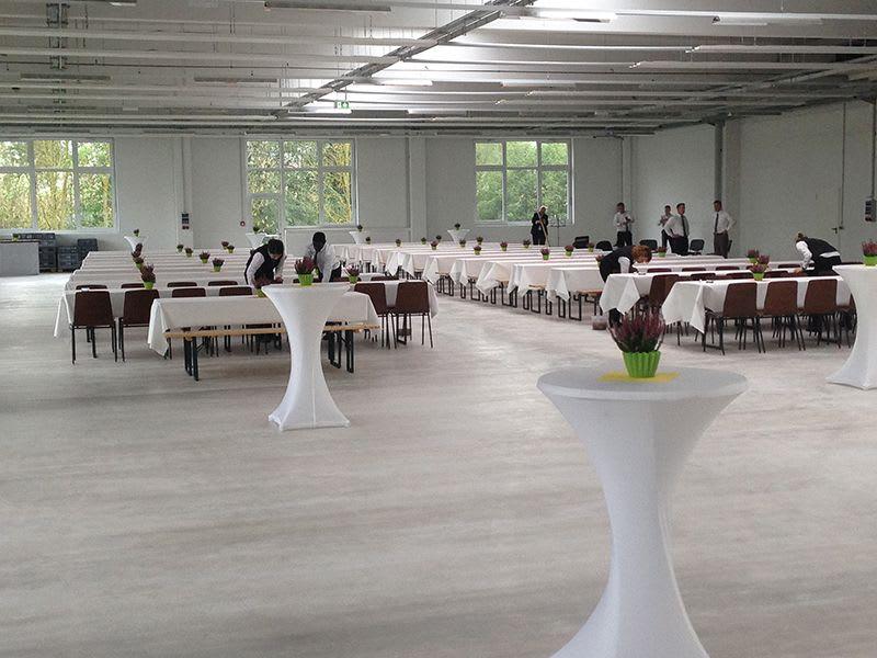 Großer Raum mit weiß dekorierten Biertischen