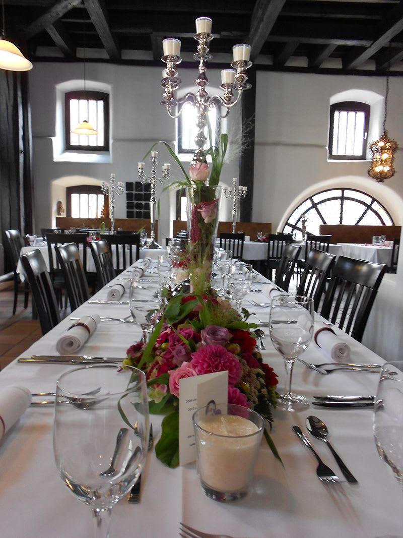 Tischdekoration mit vielen Blumen und große Kerzenständer