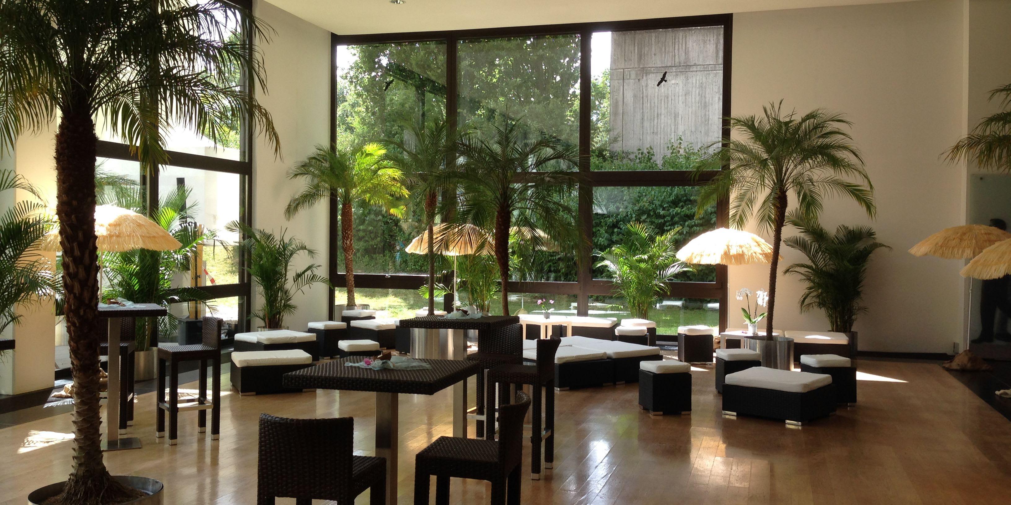 Location mit Palmen und schwarzen Strohmöbeln