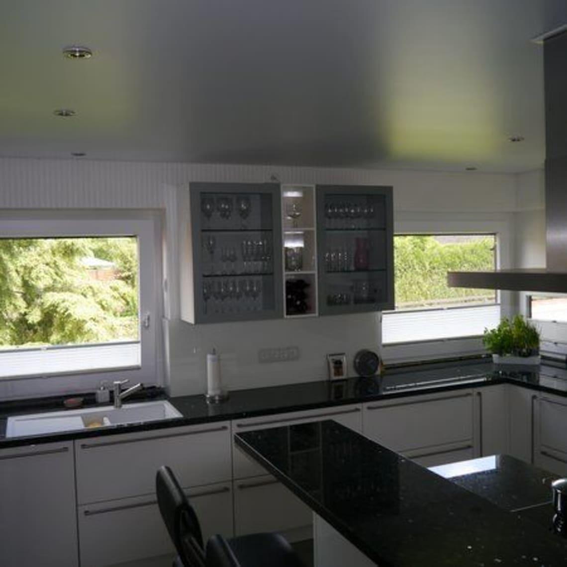 Moderne Küche mit Spanndecke und schwarzem Tisch