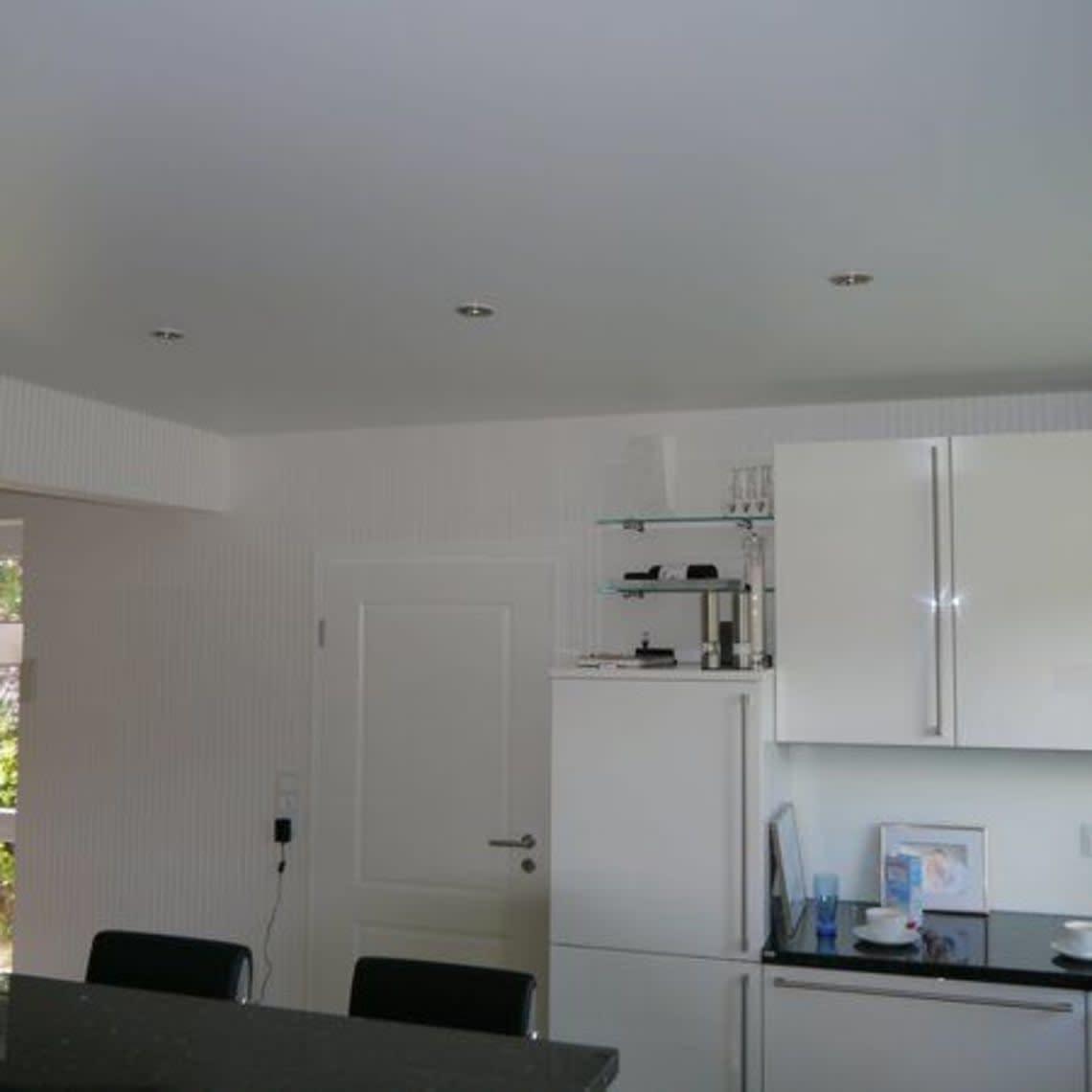 Küche mit weißer Einrichtung und Spanndecke