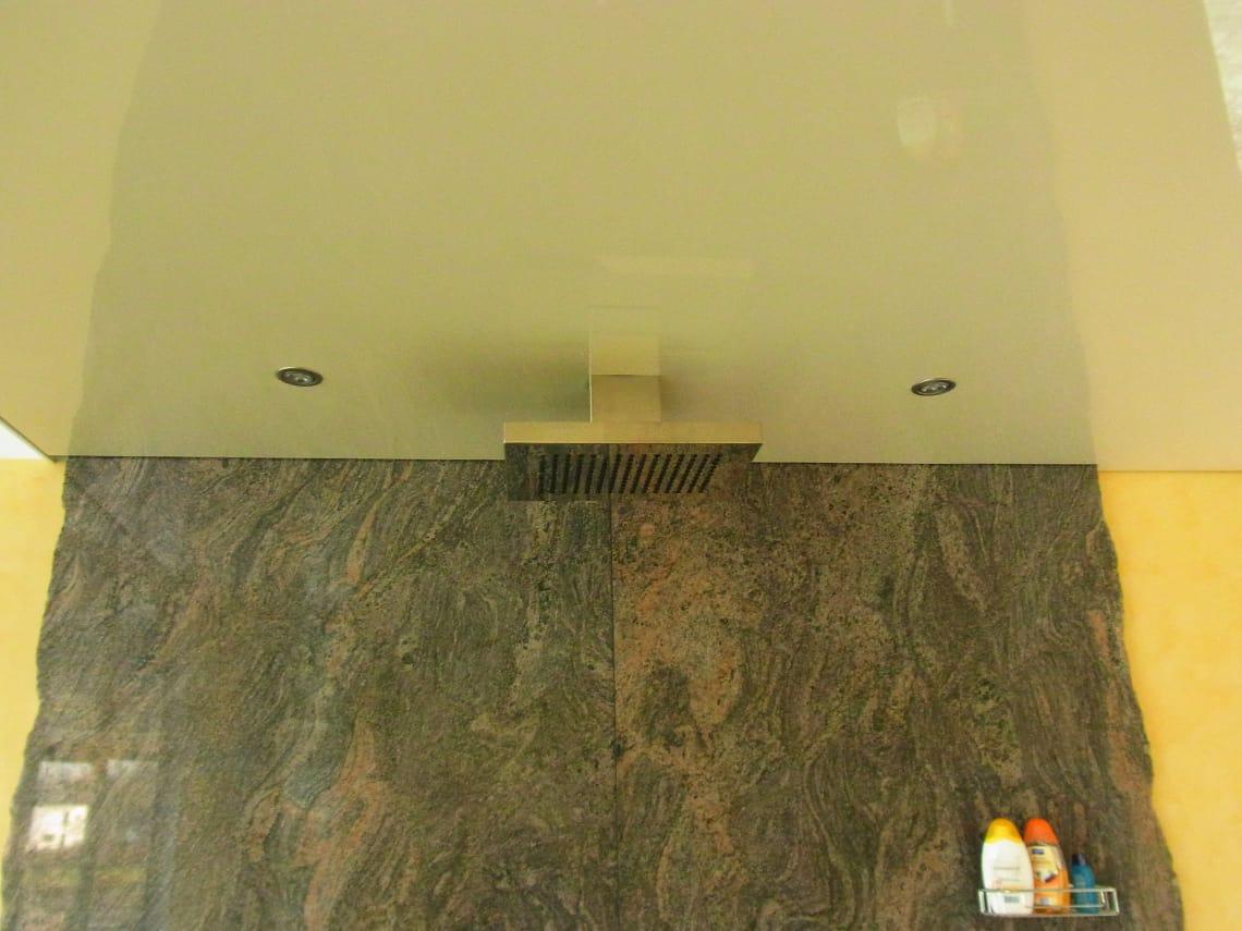 Spanndecke über einer Dusche mit Steinwand