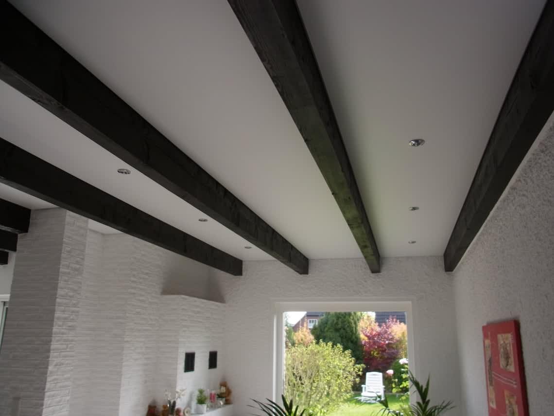 Weiße Spanndecke zwischen Dachbalken