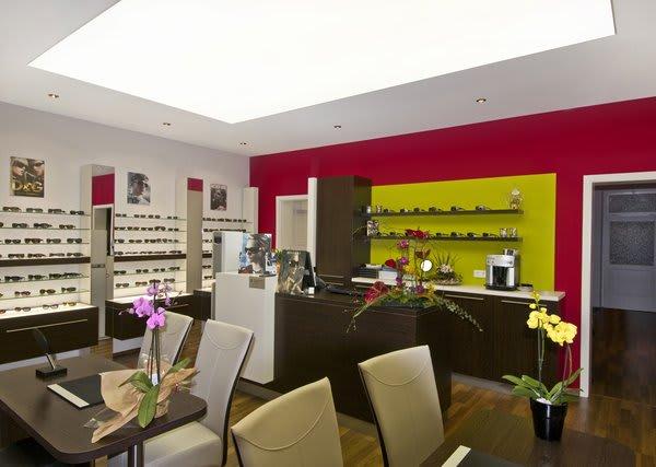 Brillengeschäft mit hellen weißen Lichtdecken und rote Wände