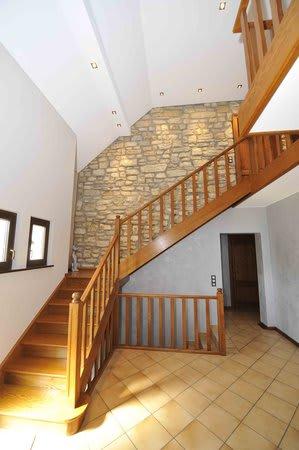 Flur mit weißer Spanndecke Holztreppe und gemauerter Wand