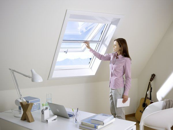 Frau am Dachfenster öffnend Insektenschutzsysteme