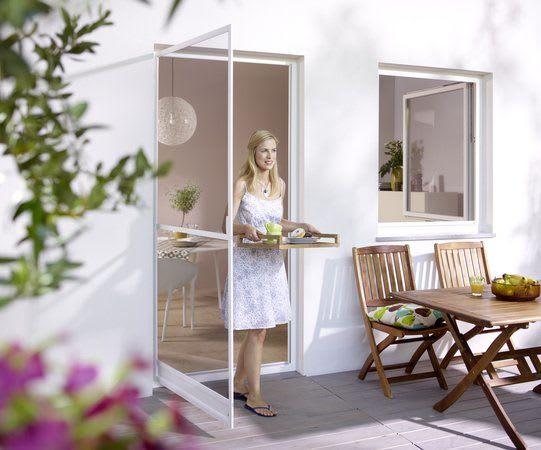 Blonde Frau kommt auf Terrasse aus Terrassentür Insektenschutzsysteme Tür