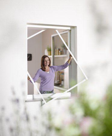 Frau am Fenster mit Insektenschutz für Fenster Spannrahmen