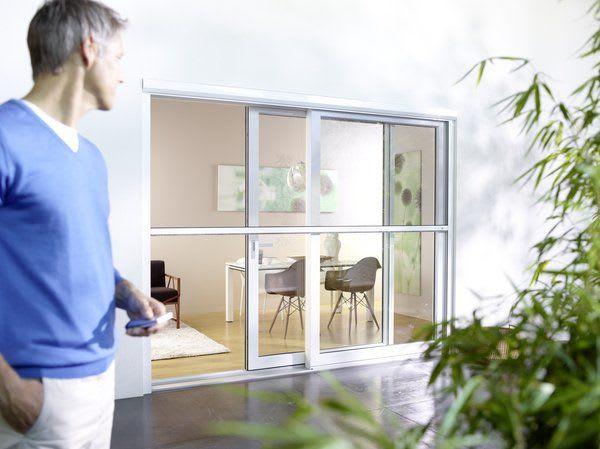 Mann auf Terrasse schaut auf Terrassentür Elektrorollo