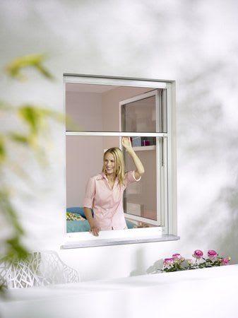 Frau am Fenster mit Rollo und Blumen
