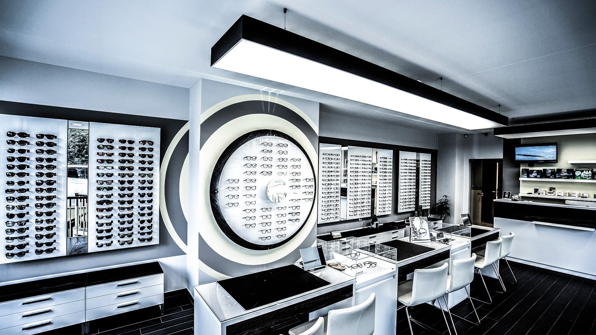 Individuell gefertigte Lichtdeckensegel für schattenfreie Beleuchtung im Ladenlokal von Optique NewLook in Luxemburg.