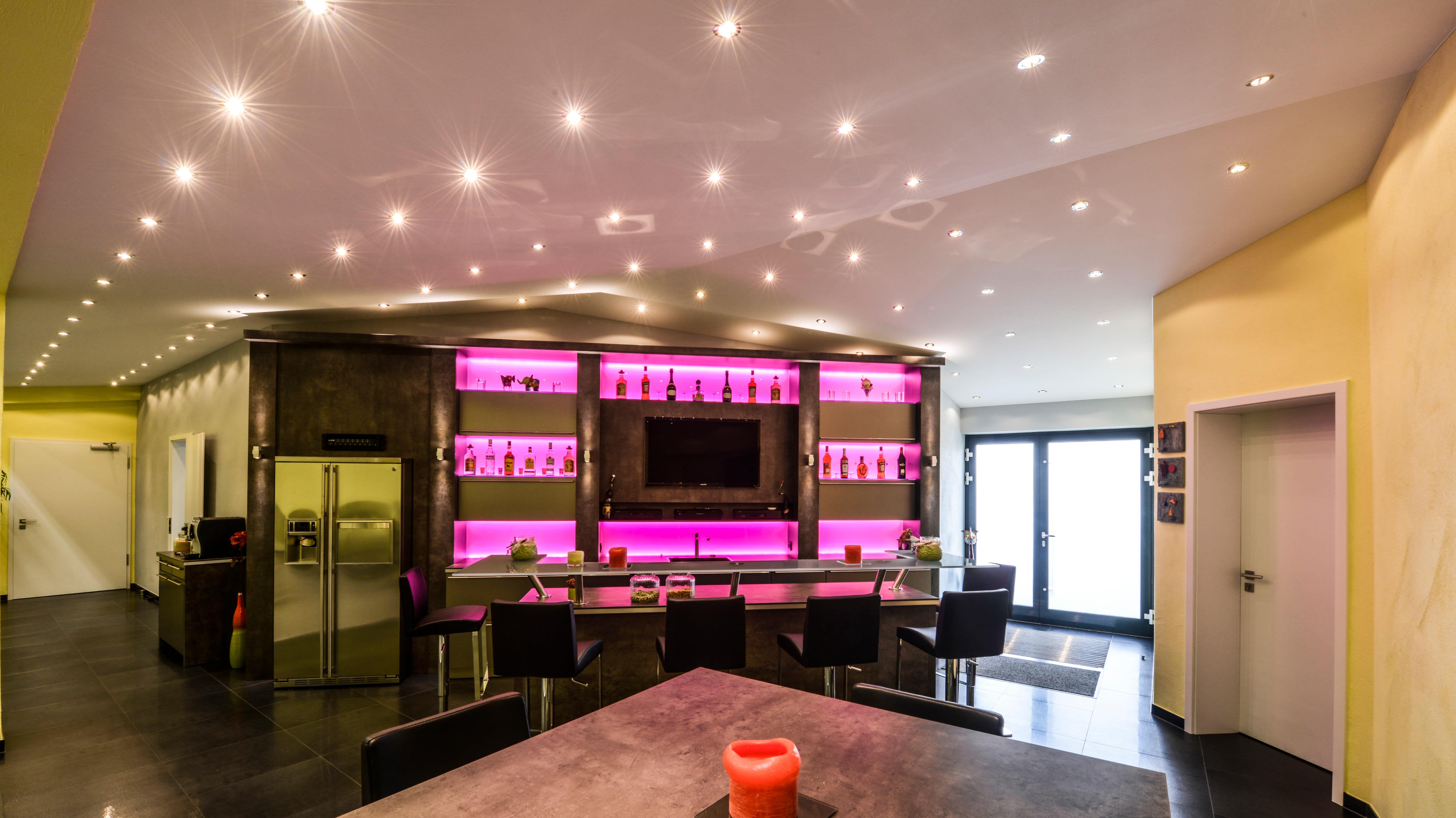 Beleuchtungskonzept im privaten Barbereich mit schicken Deckenspots sowie RGB-Hinterleuchtung hinter dem Flaschenregal.