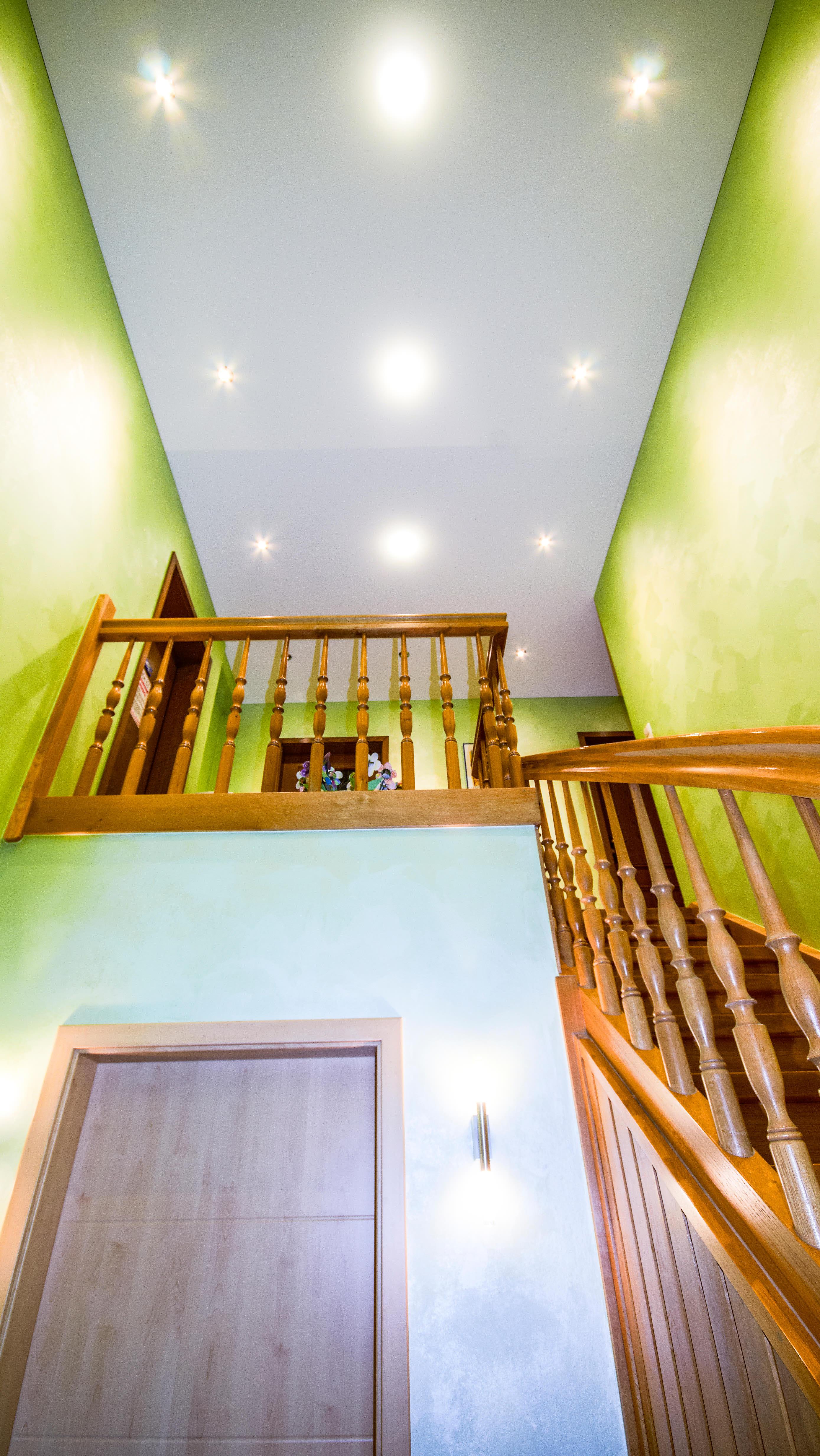 Flur mit Treppenhaus mit grünen Wänden und Beleuchtung an der Decke