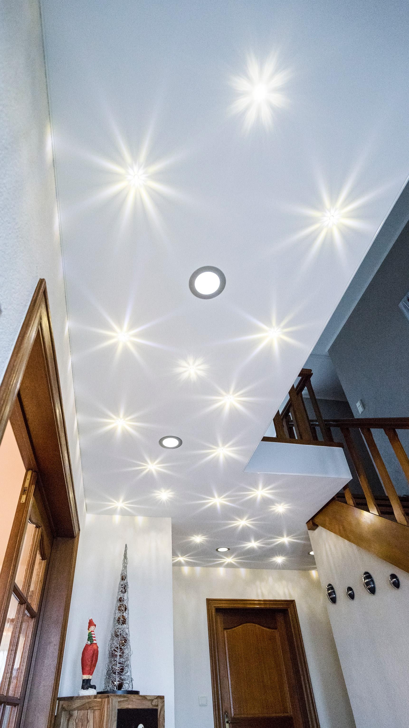 Flur mit Treppenhaus und weißen Wänden mit Beleuchtung an der Decke