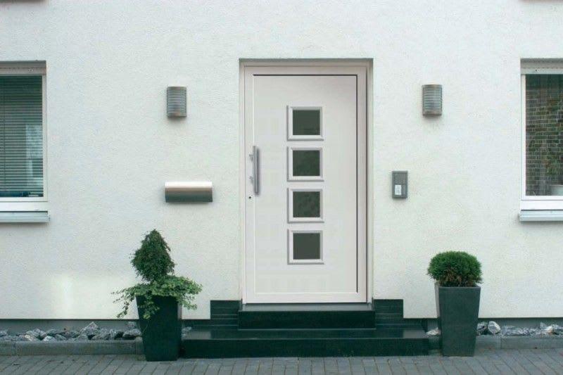Weißes Haus mit weißer Tür und zwei Fenstern