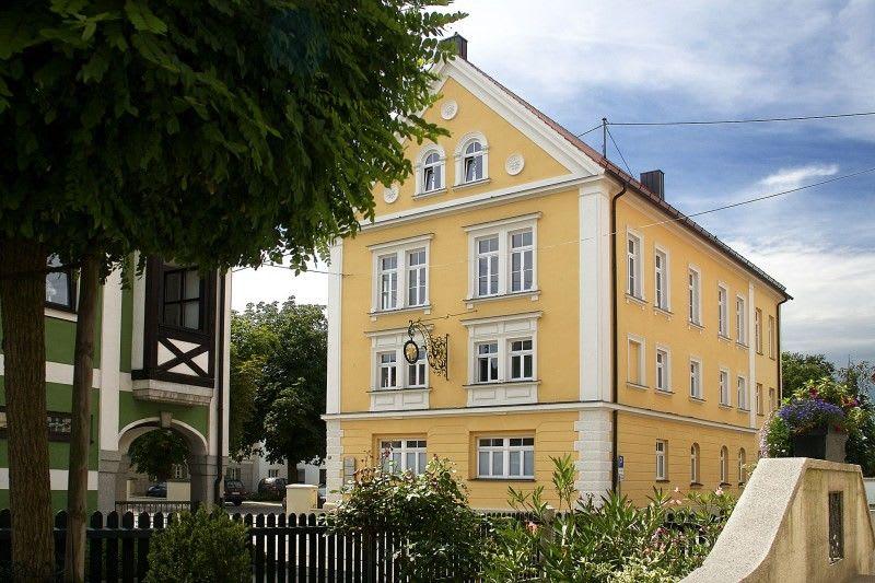 Großes gelbes Haus mit weißen Fenstern