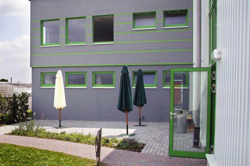 Bürogebäude grau gestrichen mit grünen Fenstern und Türen anderer Winkel