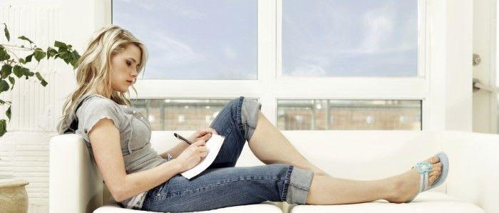 Junge blonde Frau auf dem Sofa mit Notizblock und Stift
