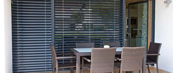 Tisch auf dem Balkon mit großem Fenster im Hintergrund und Rolladen