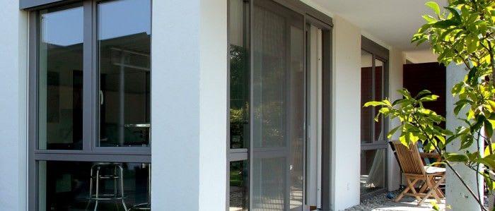 Haus mit verschiedenen Fenstern und Insektenschutz