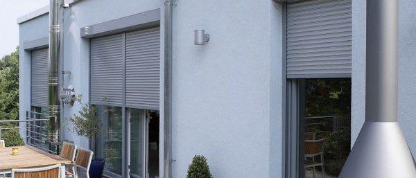 Weißes Haus mit grauen Fensterrahmen und Rolladen
