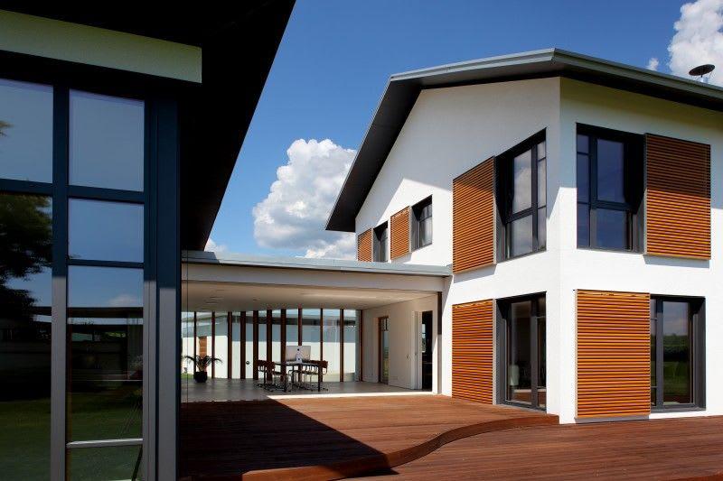 großes weißes Haus mit Holzverzierung und großem Durchgang
