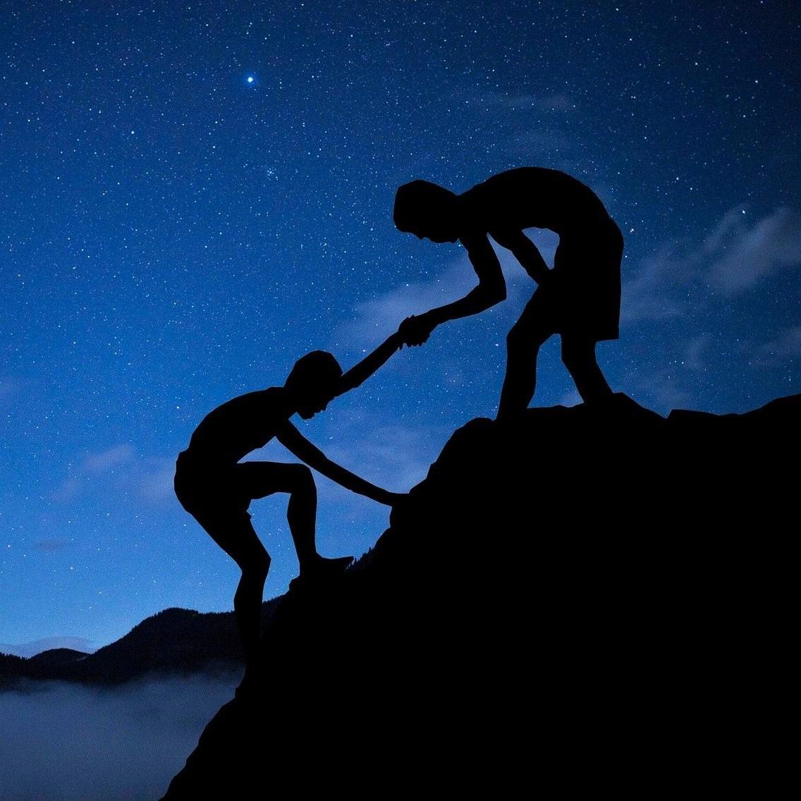 Ein Mensch hilft einem anderen auf einen Berg