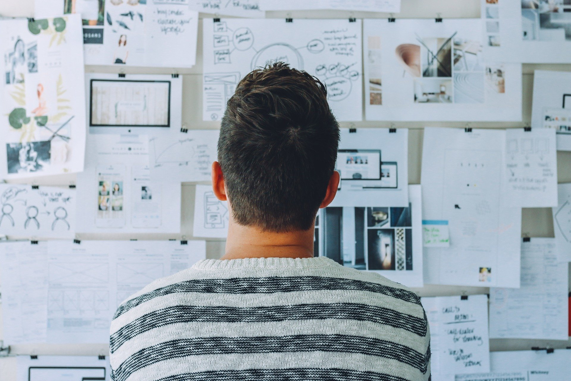 Mann schaut auf Pinnwand mit Plänen