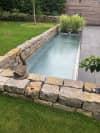 Garten mit Wasserspiel und Steinmauer