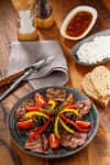 Minutensteaks, mit Paprika und Tomaten garniert