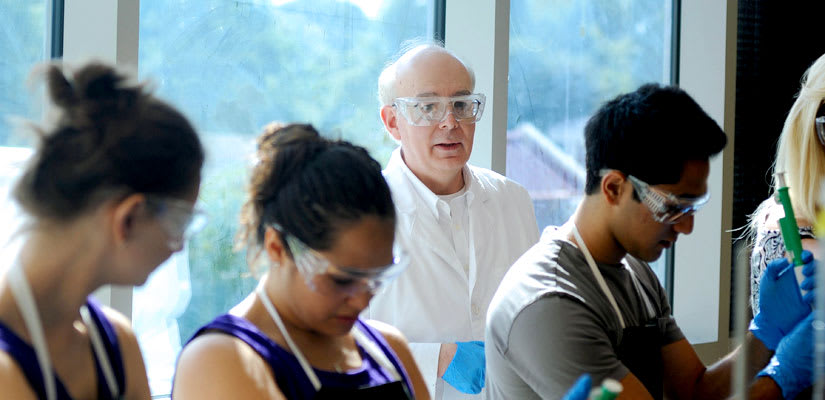 Professor Dennis Merat with a group of student in a chemistry class