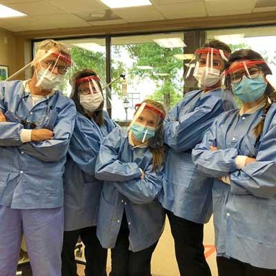 CBU Alum and office staff wear face shields