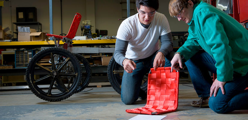 two engineering students work on a seat for a moon buggy