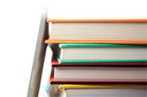 ipad leaning on stack of books