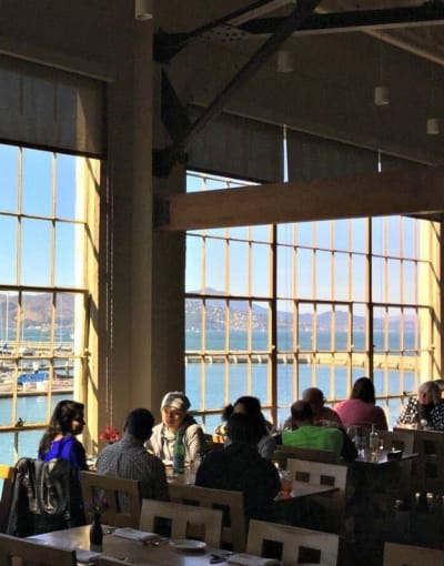 Locals and tourists dining at a waterfront restaurant in San Francisco