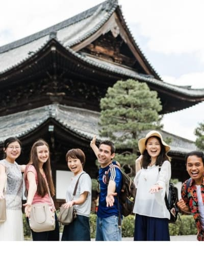 Group of tourists posing with their local guide at a popular temple in Kyoto