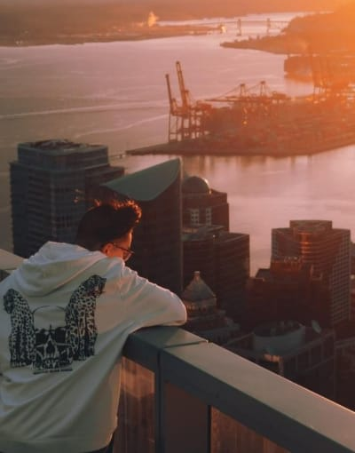 Tourist enjoying the sunset from a viewing platform on a building in Vancouver