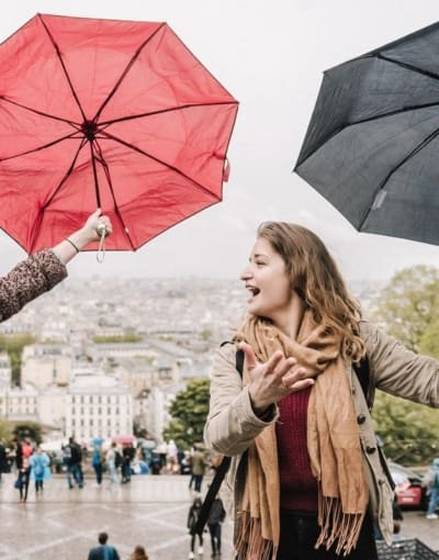 Tourist enjoying a rainy day of exploring Paris with a local guide