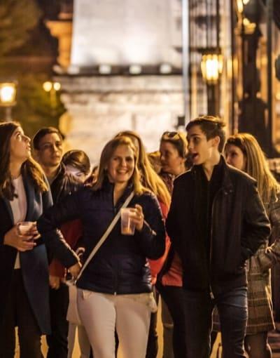 Group of tourists walking along a pedestrian bridge on a night tour of Budapest