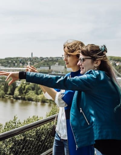 Tourists taking in the sights of Prague on a bridge over the Vltava river
