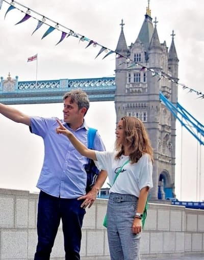 Local guide pointing out popular attractions to a tourist in London with Tower Bridge in the background