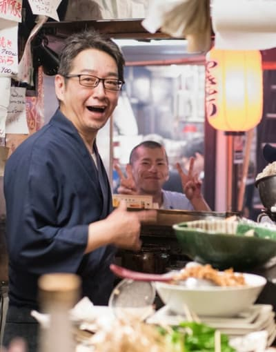 Tourists enjoying a meal with a local guide at a busy restaurant in Japan