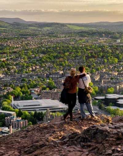 Tourists enjoying the views of Edinburgh below from Arthur's Seat