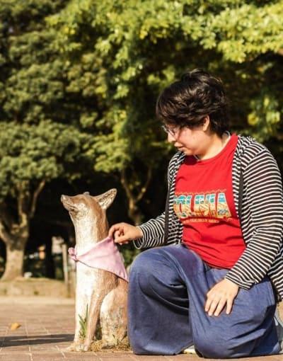 Tourists crouching down next to the fox statues in Ohori park Fukuoka