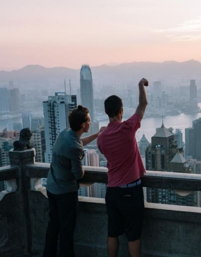 Local guide pointing out famous buildings to a tourist from a viewpoint overlooking Hong Kong