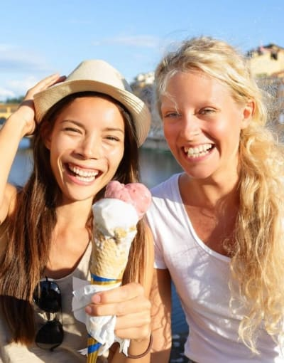 Smiling tourists holding cones of gelato on a bridge over a canal in Florence